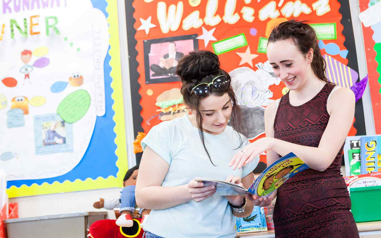 Two students reading a book in primary education classroom