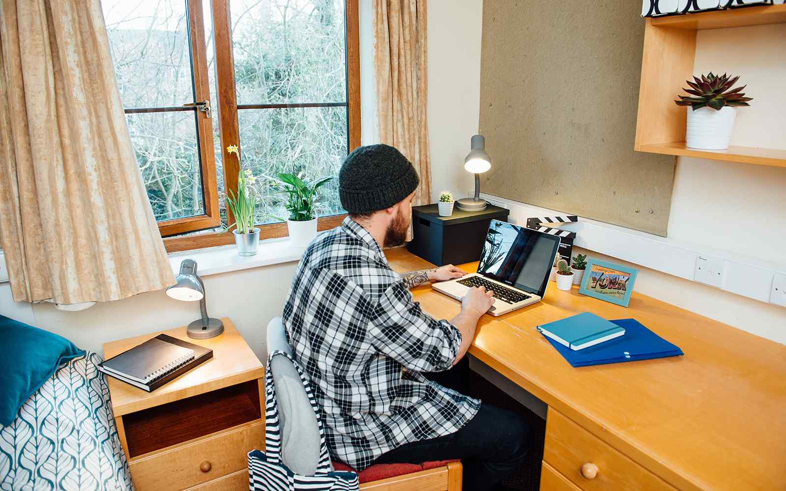 A student working on a laptop from accommodation at Limes Court
