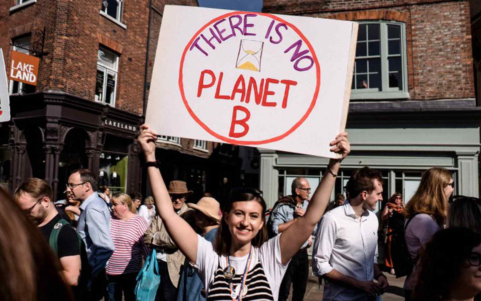 A smiling student holding a placard