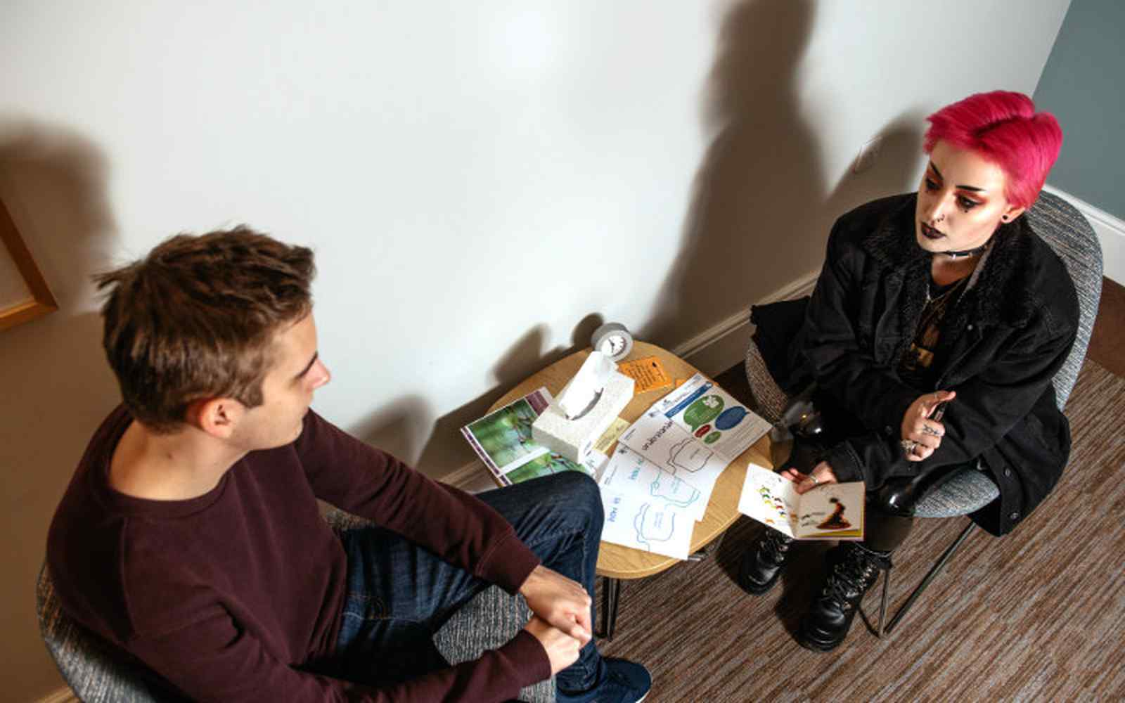 2 people sitting facing each other in a counselling session