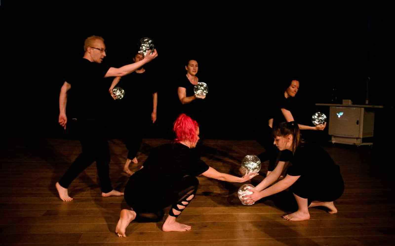Theatre performers dressed in black, holding lit globes