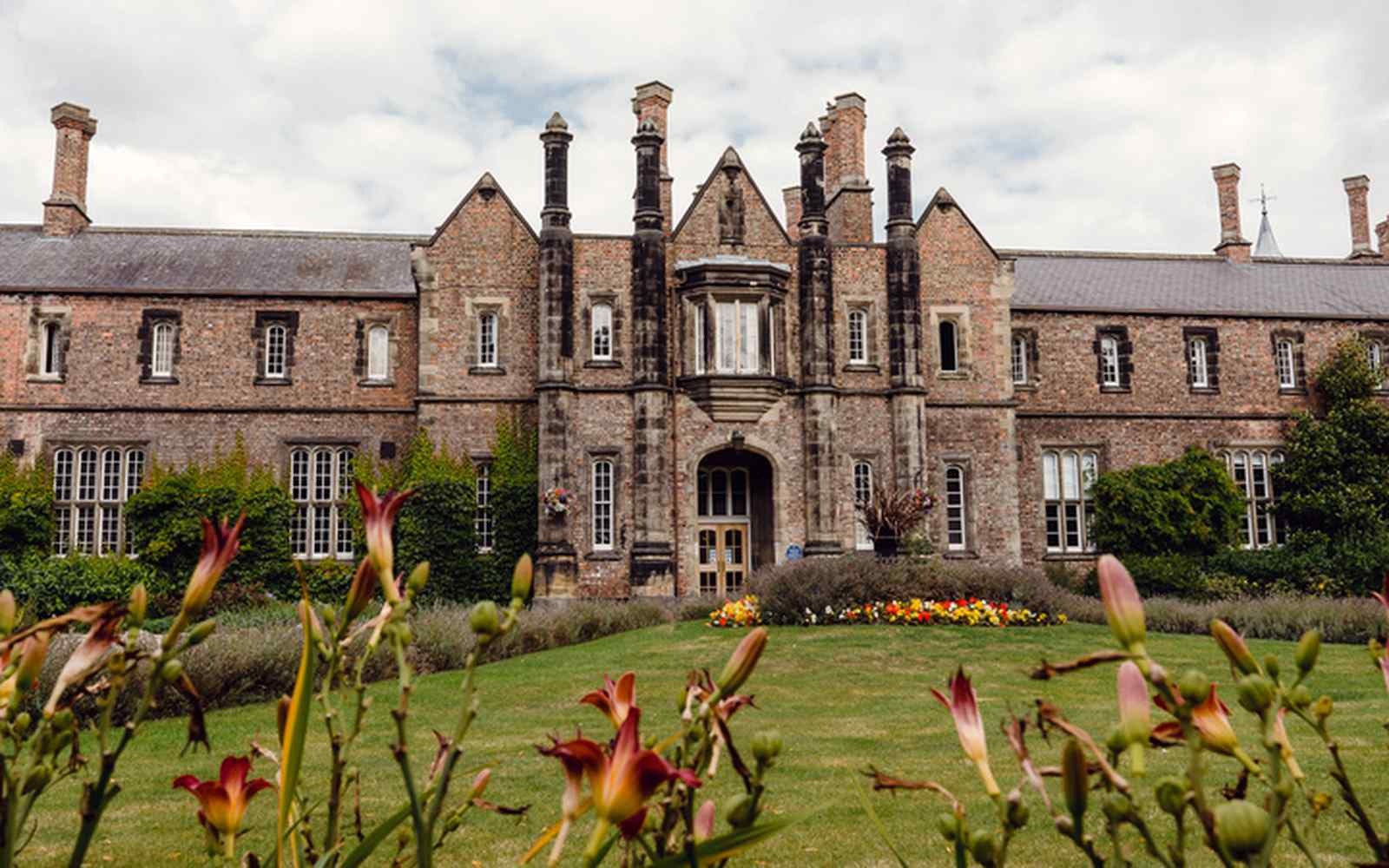 A wide shot of the historic front of YSJ with lawns and flowerbeds in the foreground