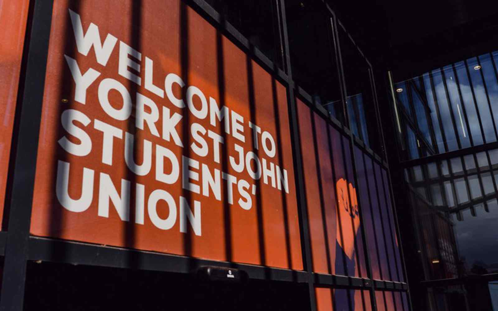 A close up of a red and white sign for York St John SU