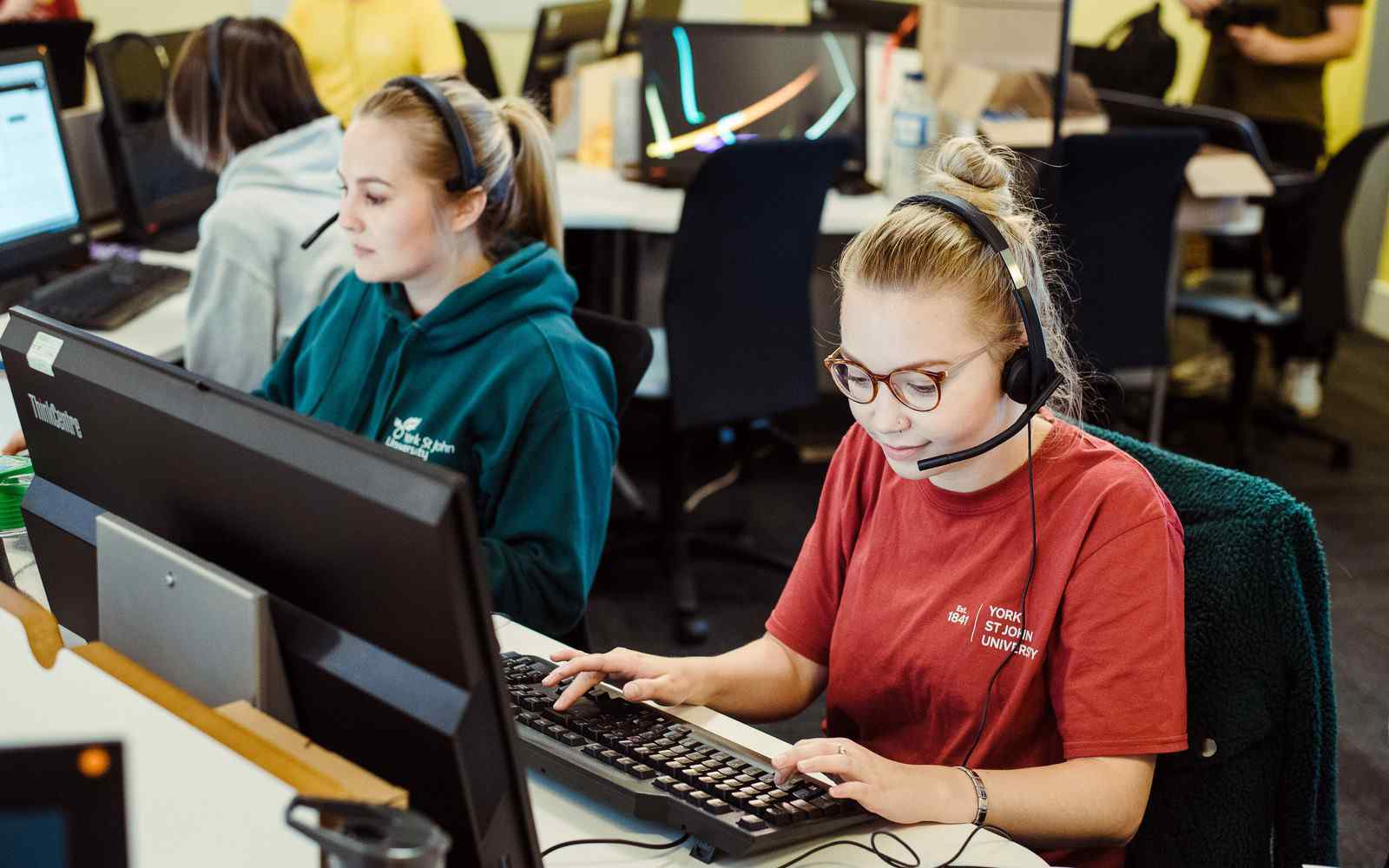 A call centre with 2 women at computers talking into headsets