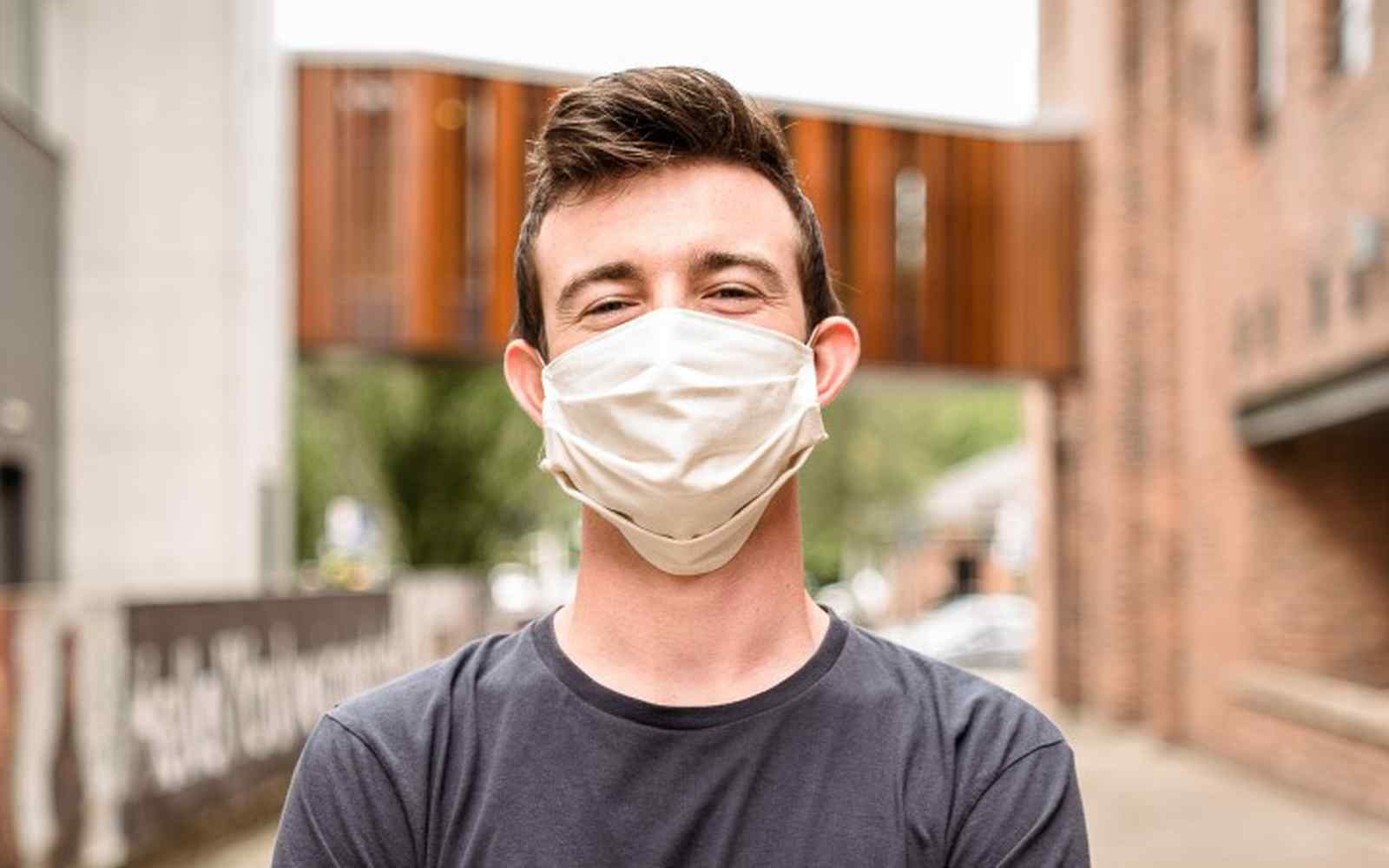 Male student in a white face mask on campus