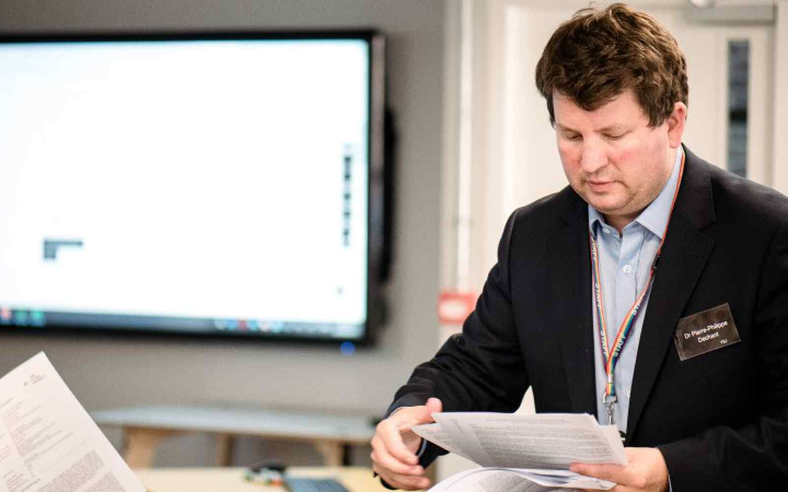 A smartly dressed man working in front of a large computer screen