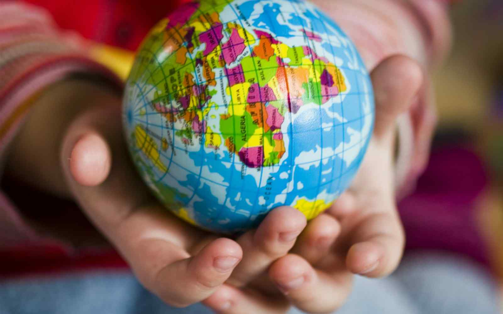 A child holding a globe in their hands