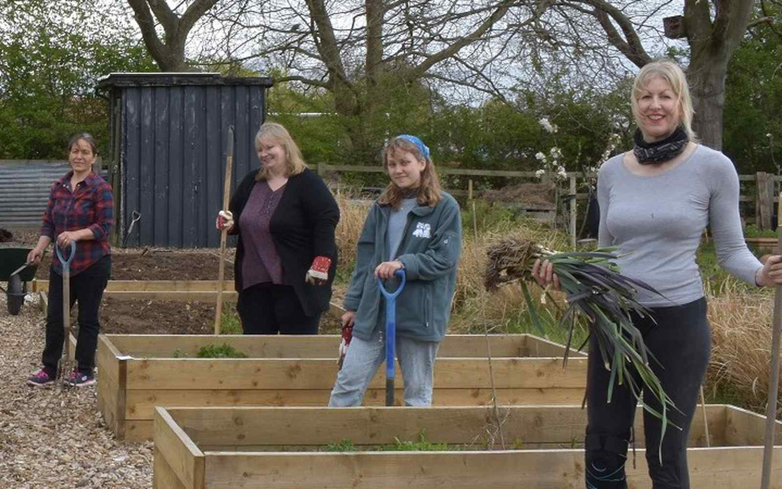 People outside at allotment garden holding produce