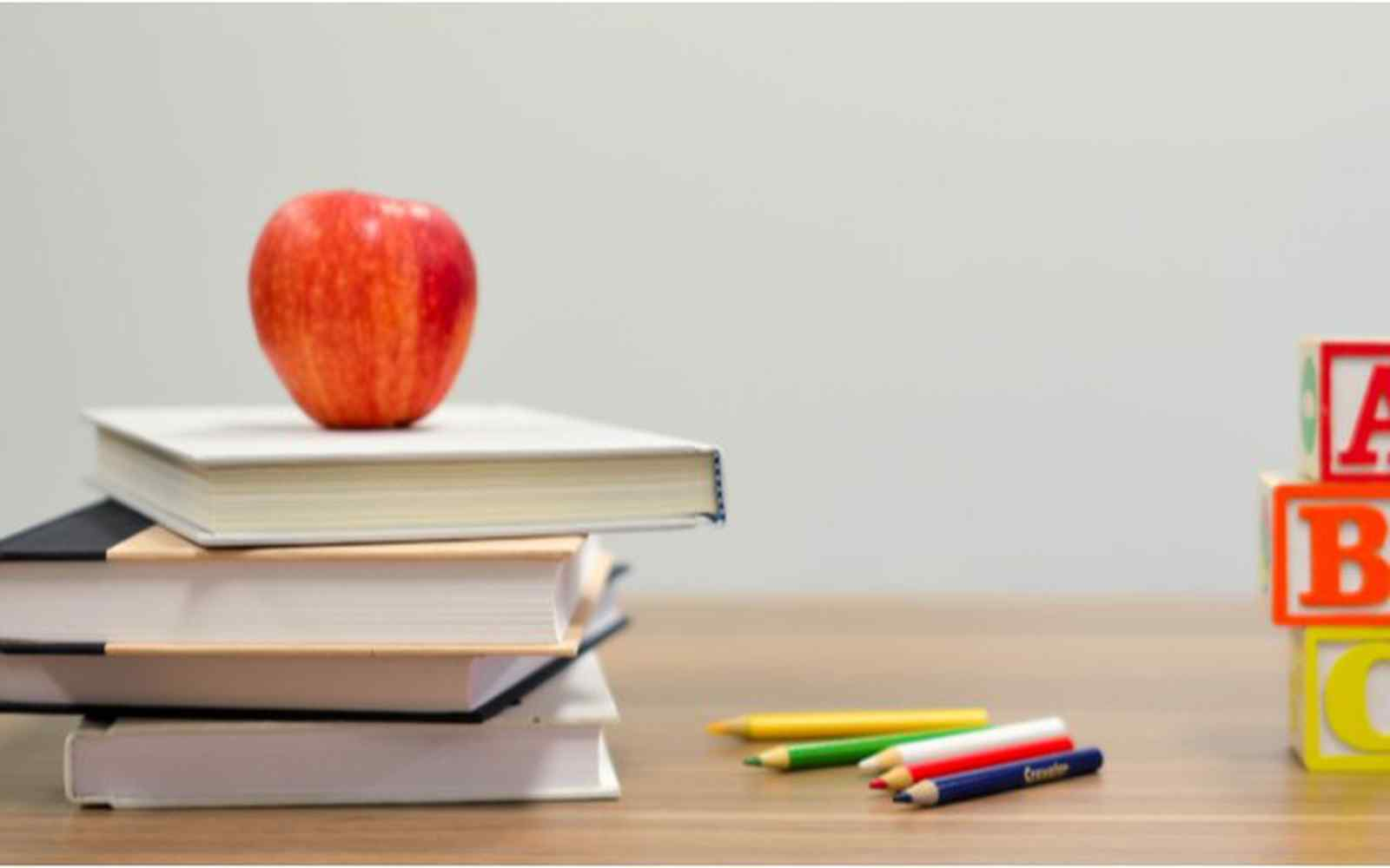 Red apple on stack on books next to crayons