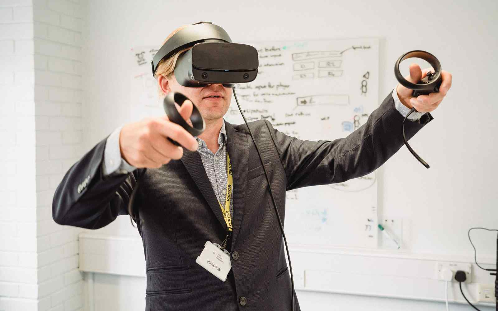 A man wearing a VR headset and hand controls