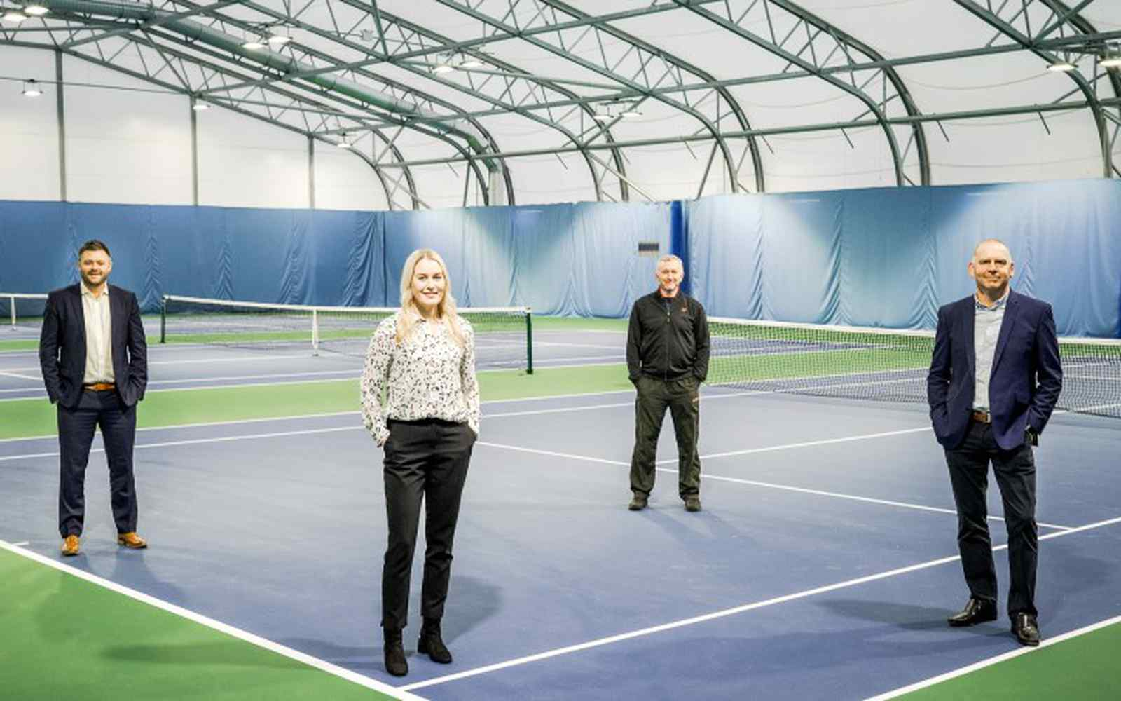 Four smartly dressed people on an indoor tennis court