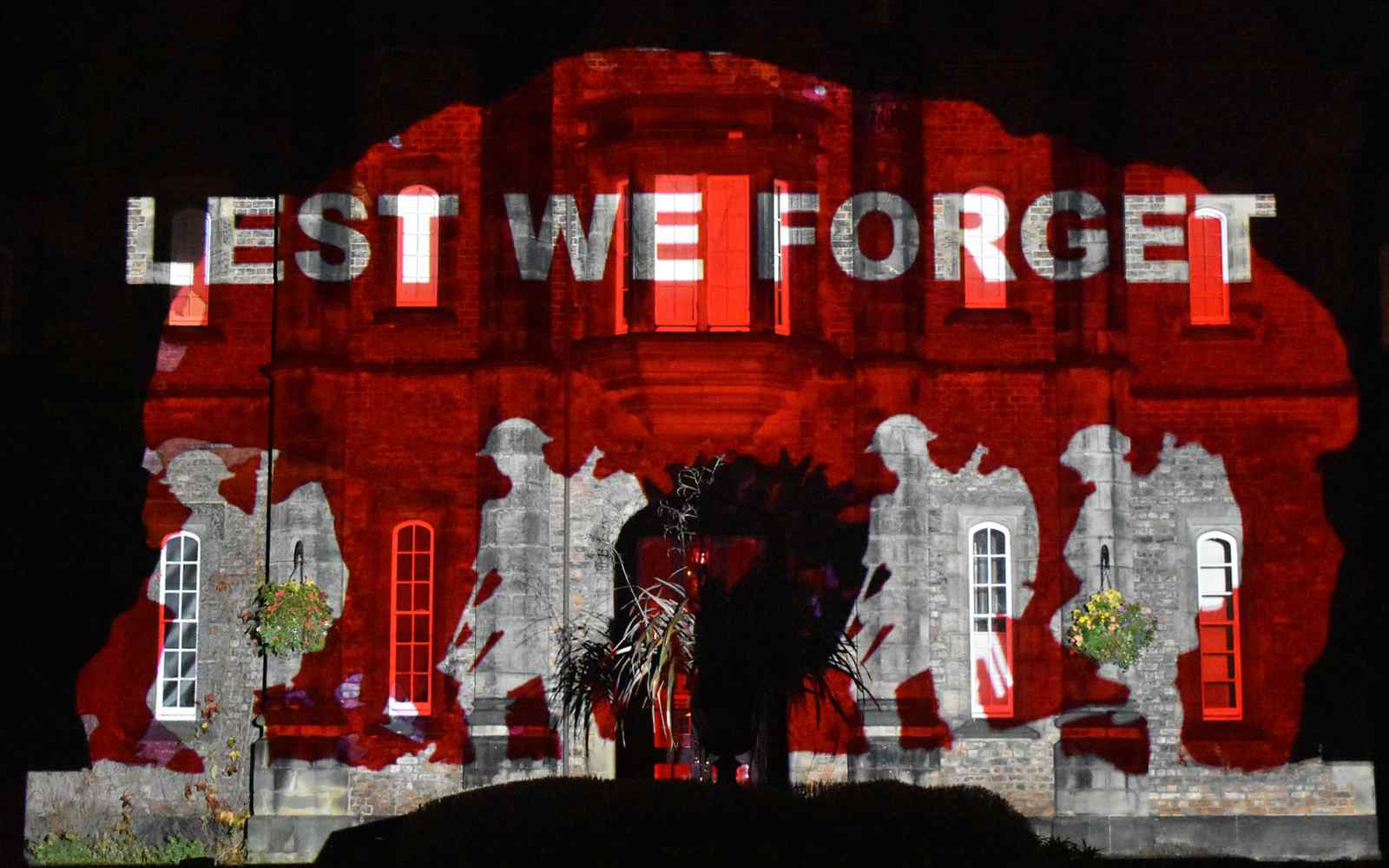 Poppy themed light projection onto Lord Mayor's Walk campus building
