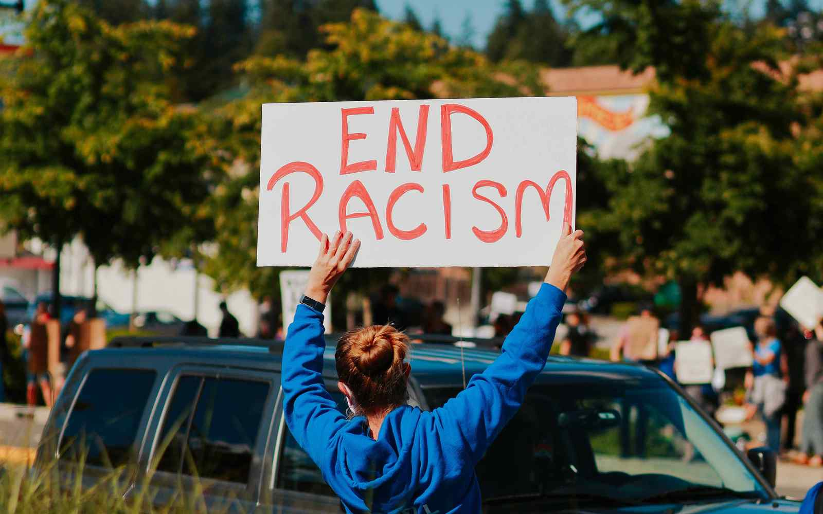 woman holding a handwritten sign saying end racism