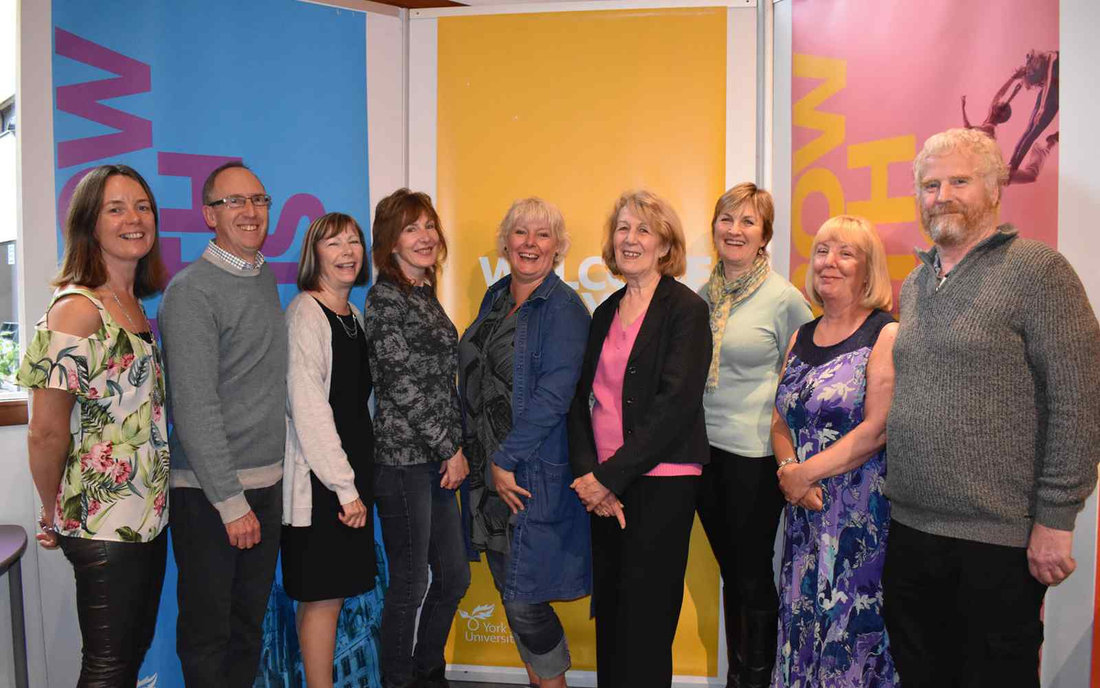 9 people standing in front of coloured background