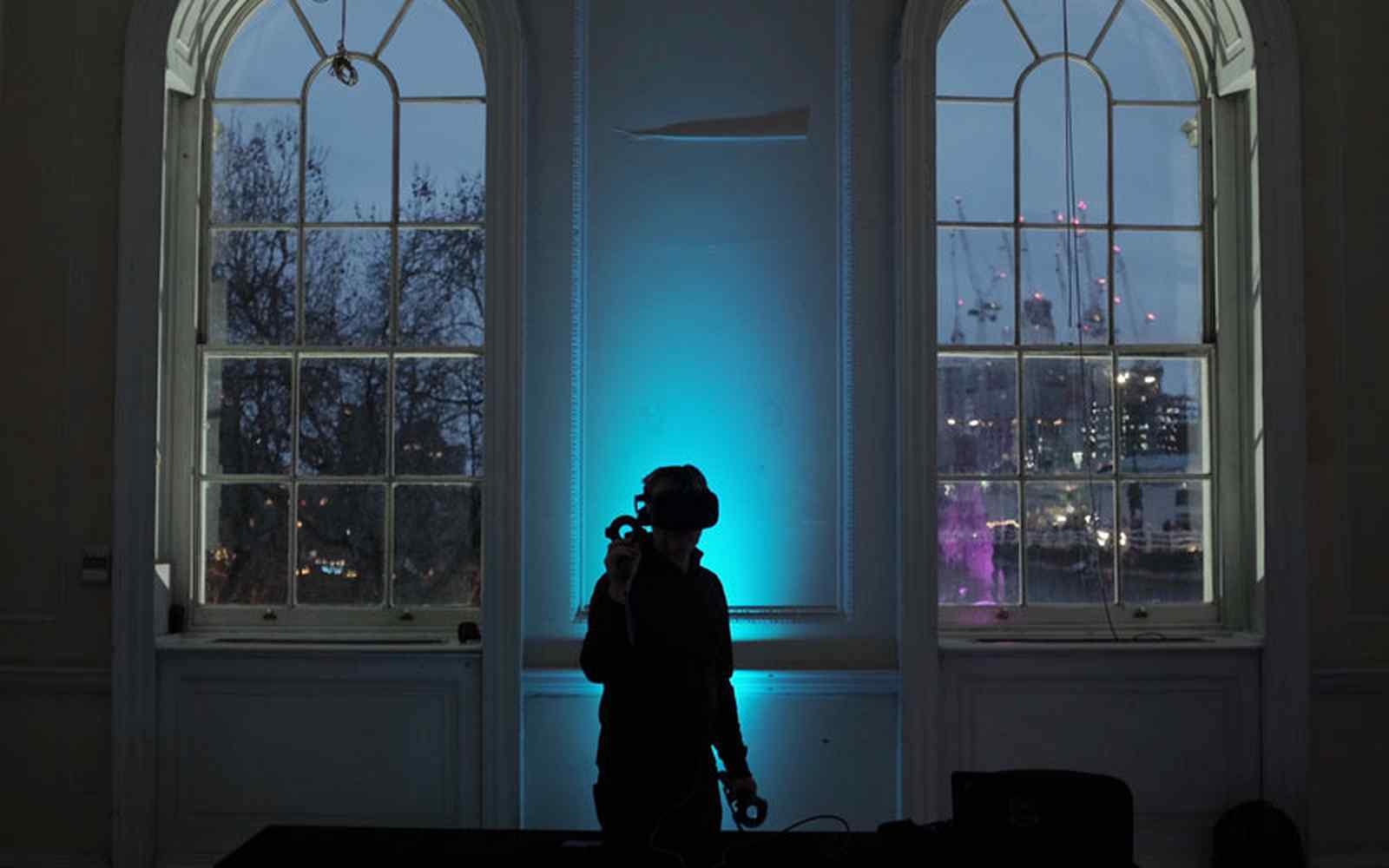 Person in Virtual Reality headset standing in front of two windows at Somerset House