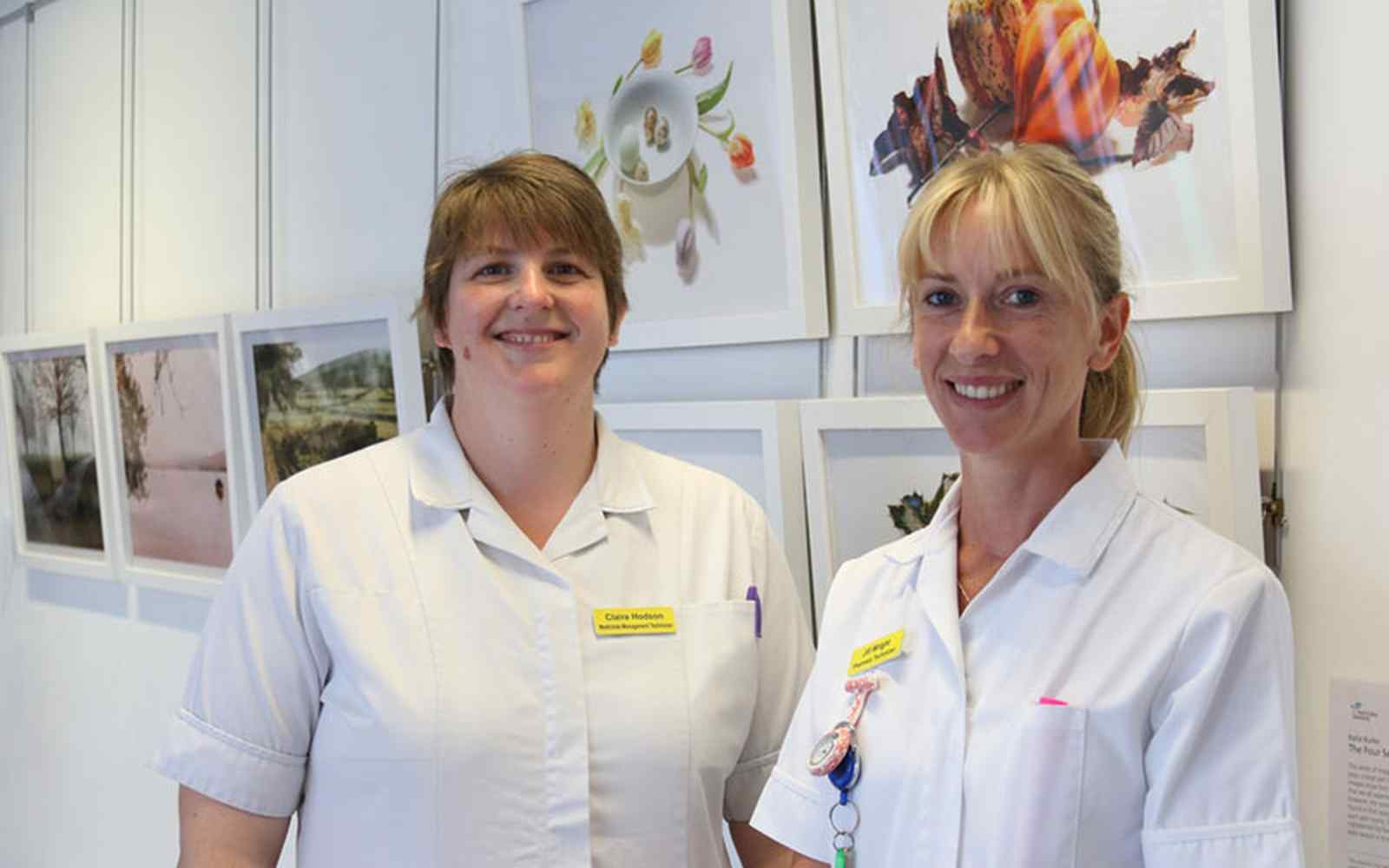 NHS Technicians in front of students' photography exhibition