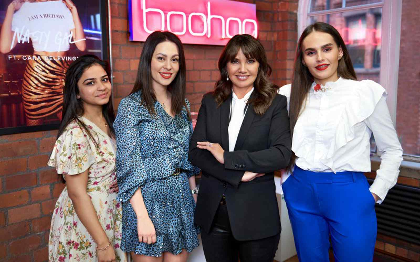 boohoo founder Carol Kane posing with 3 female fashion students in front of an neon sign
