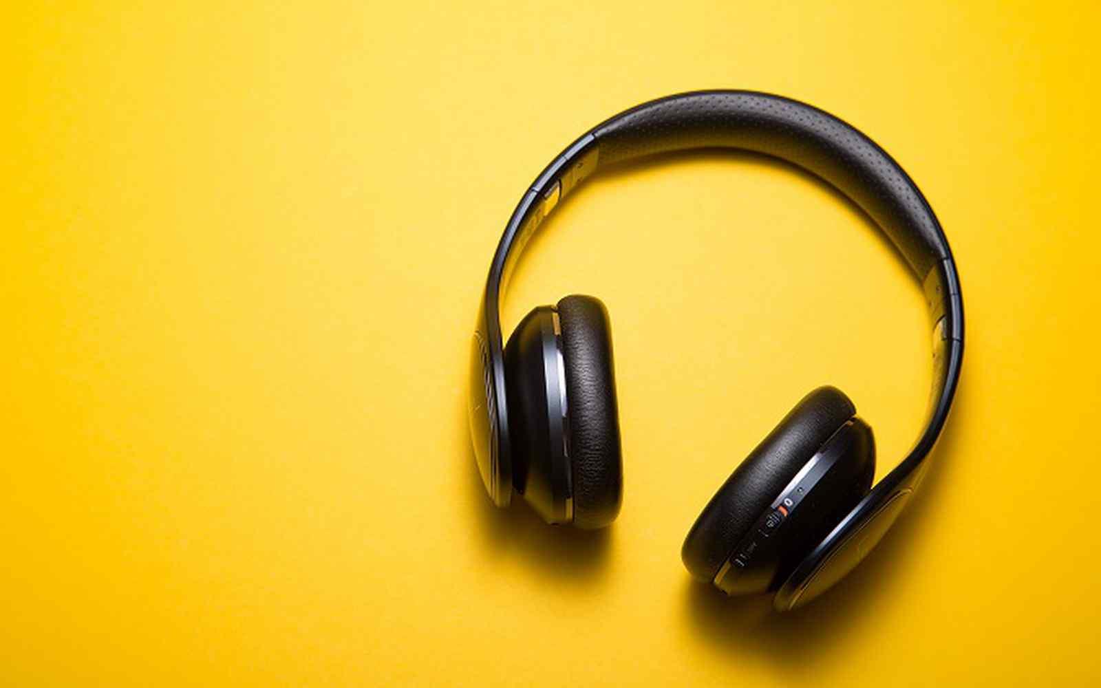 Black music headphones with yellow background