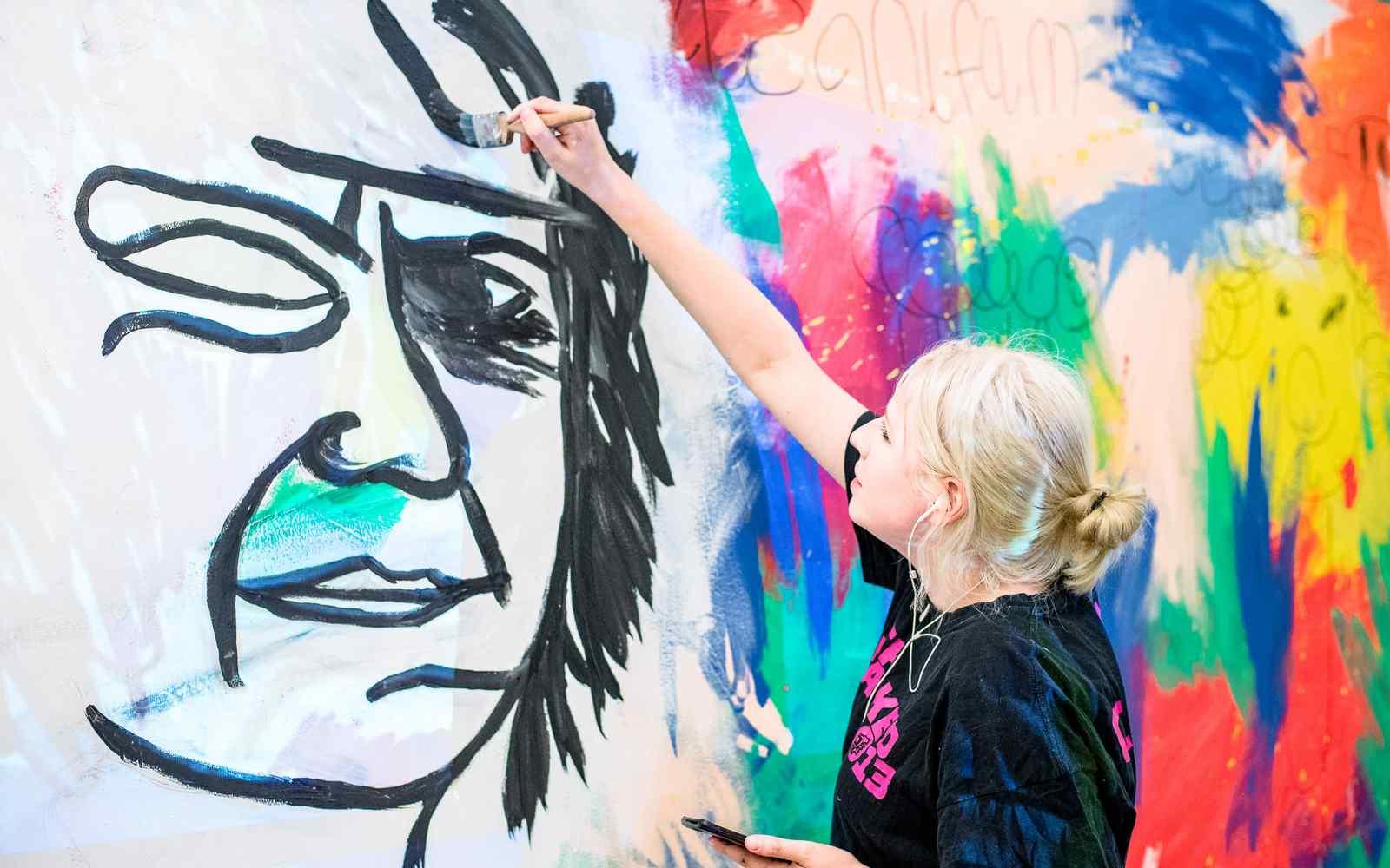 A student installing artwork