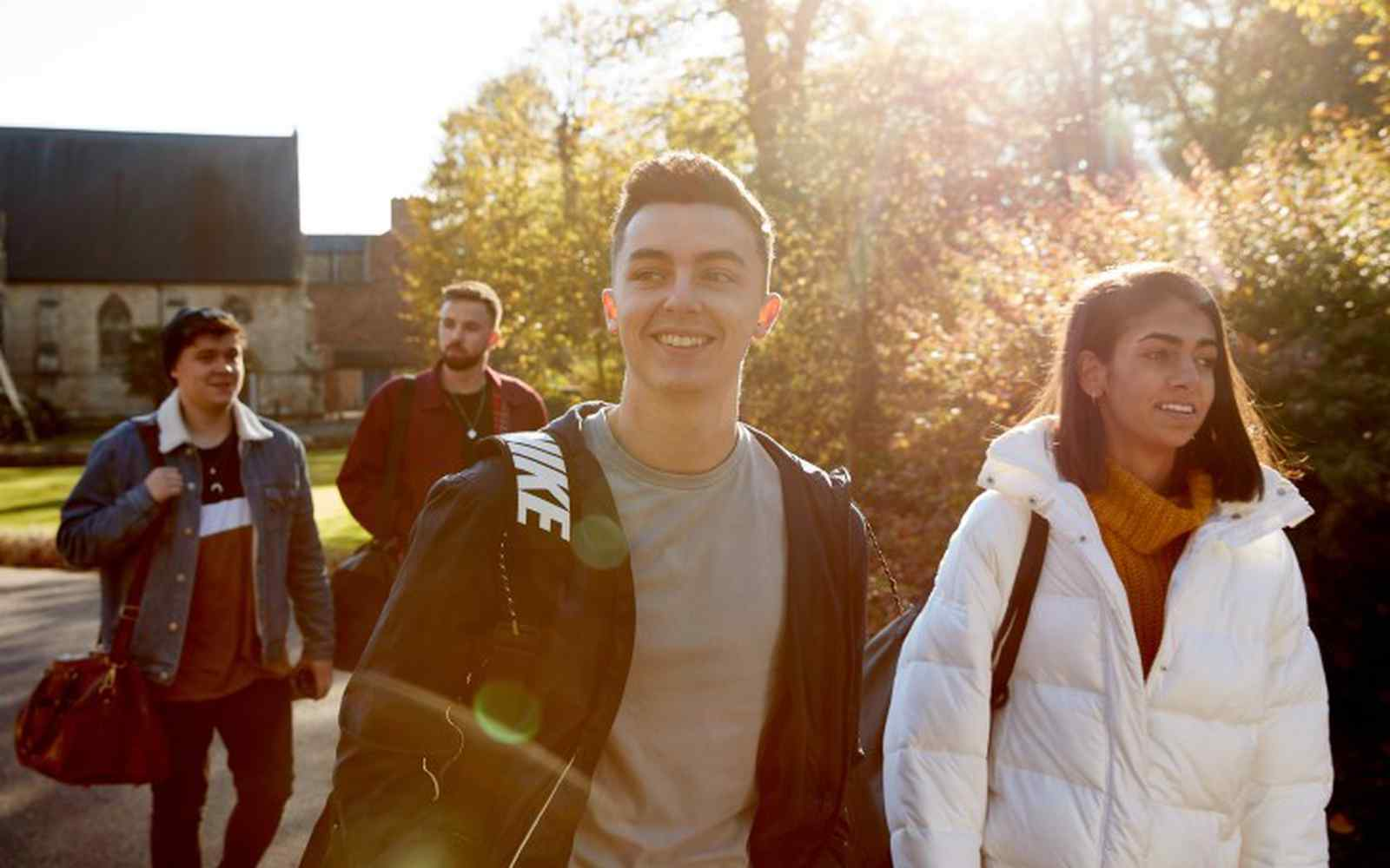 A group of students smiling outside campus