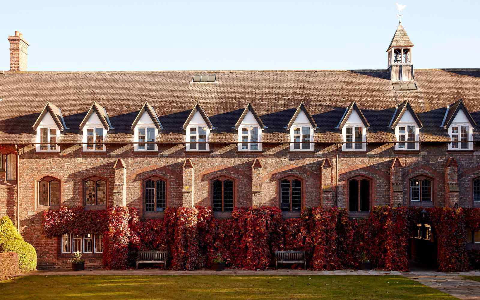 View of the brick buildings of the historic quad on campus, with autumnal leaves.