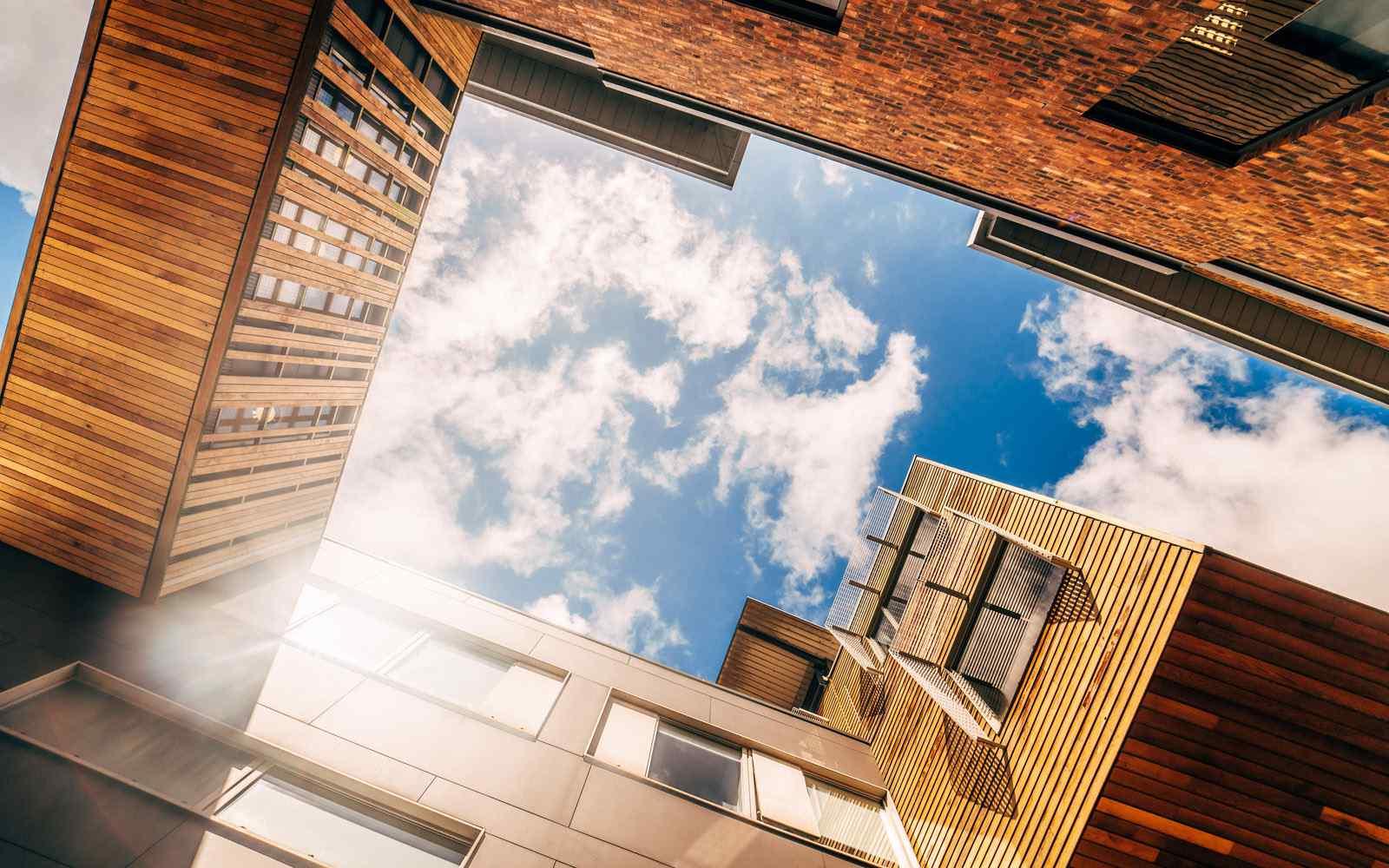 Looking up between campus buildings to see blue sky.