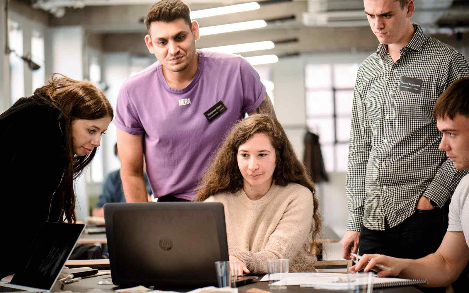 Data science students gathered around a laptop at the London Campus