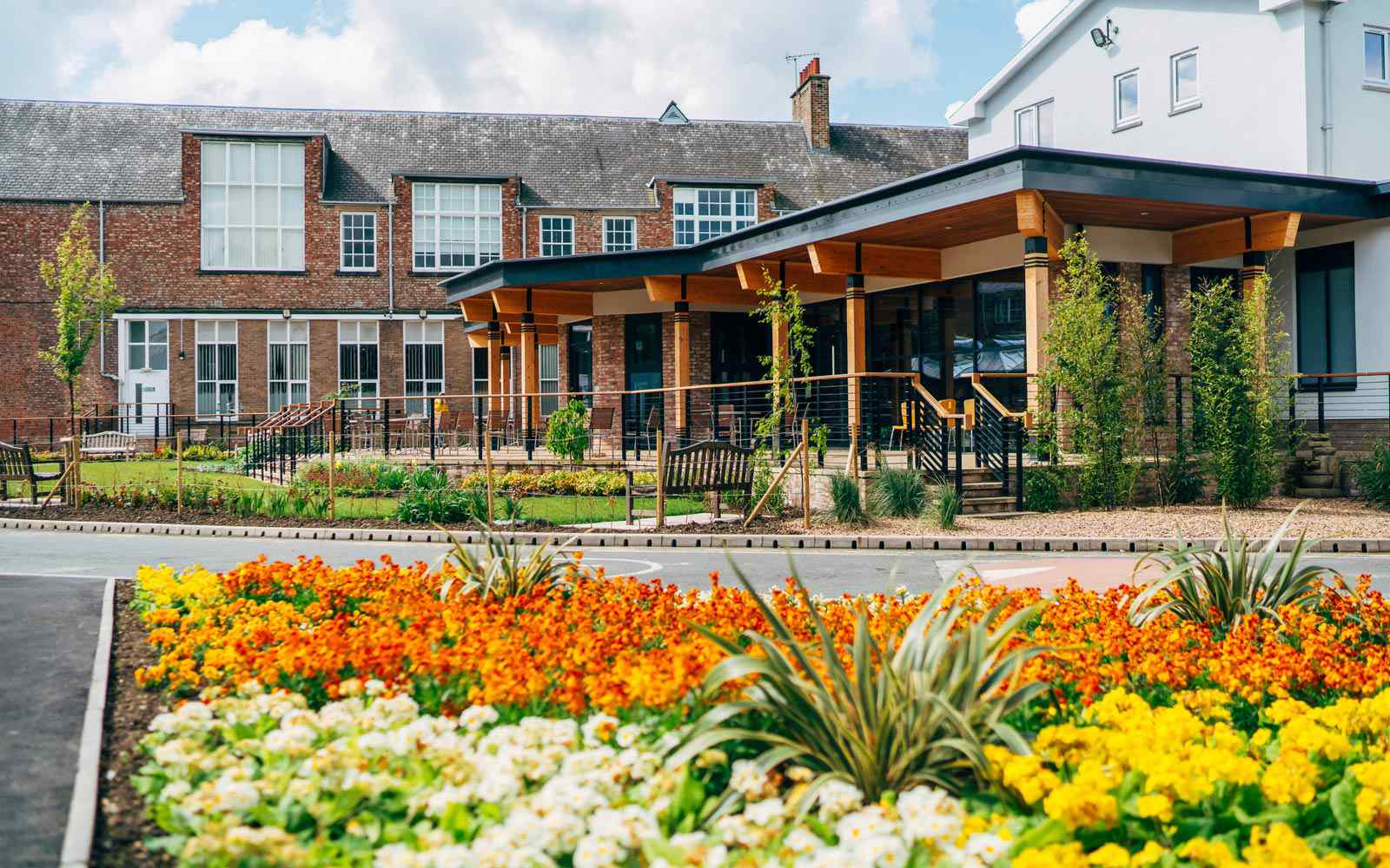 View of the dining room building on campus with orange and yellow flowers in the foreground