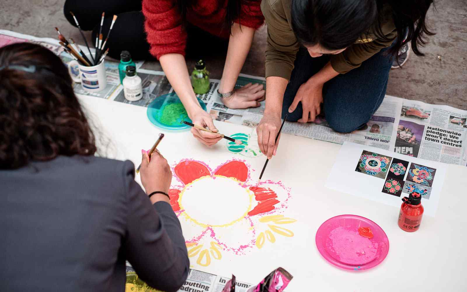 Students working together to paint flower