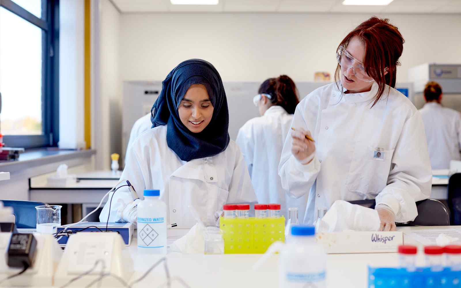 Two health science students working in labs
