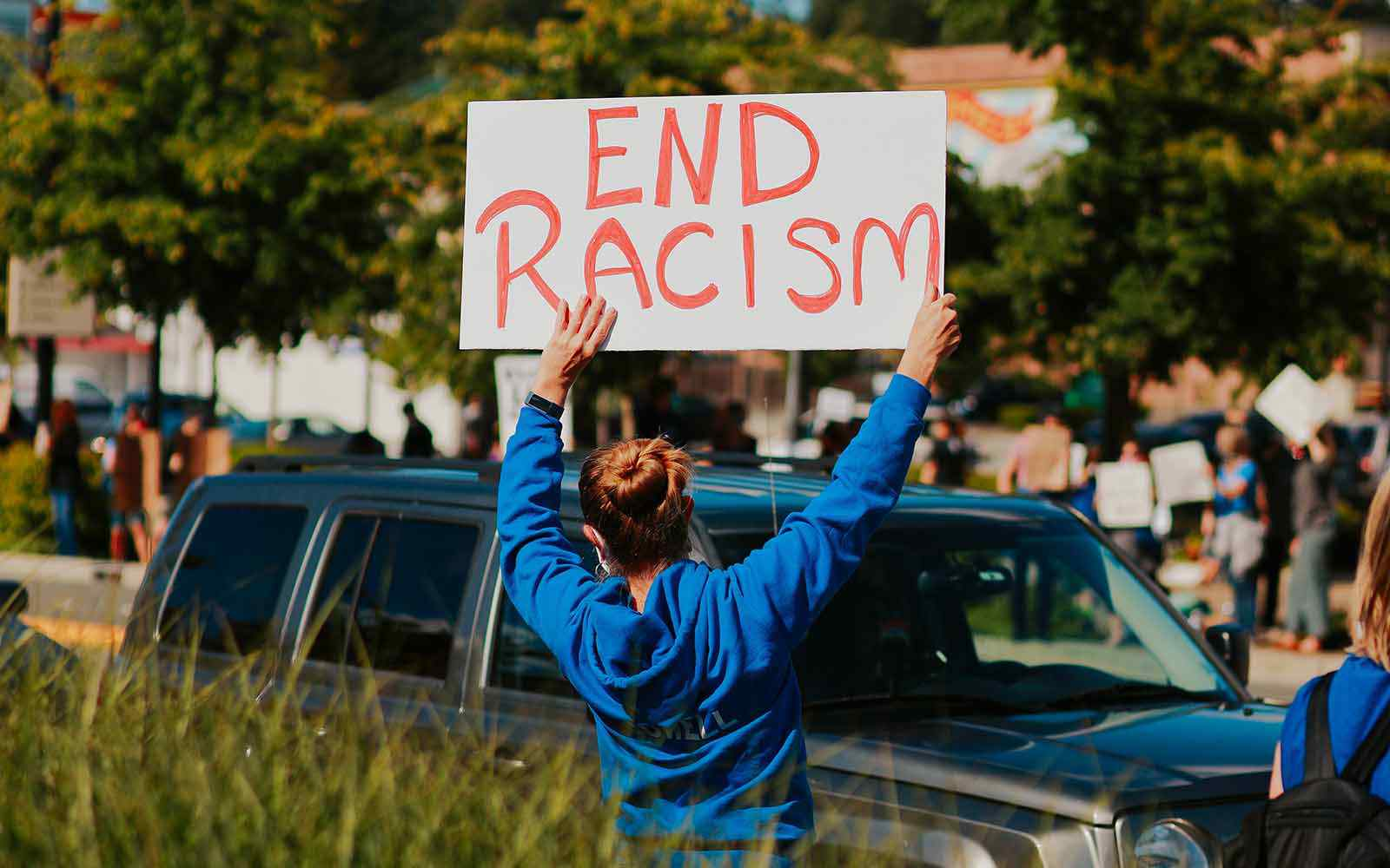 Person in blue jacket outside holding up a sign saying 'End Racism'.