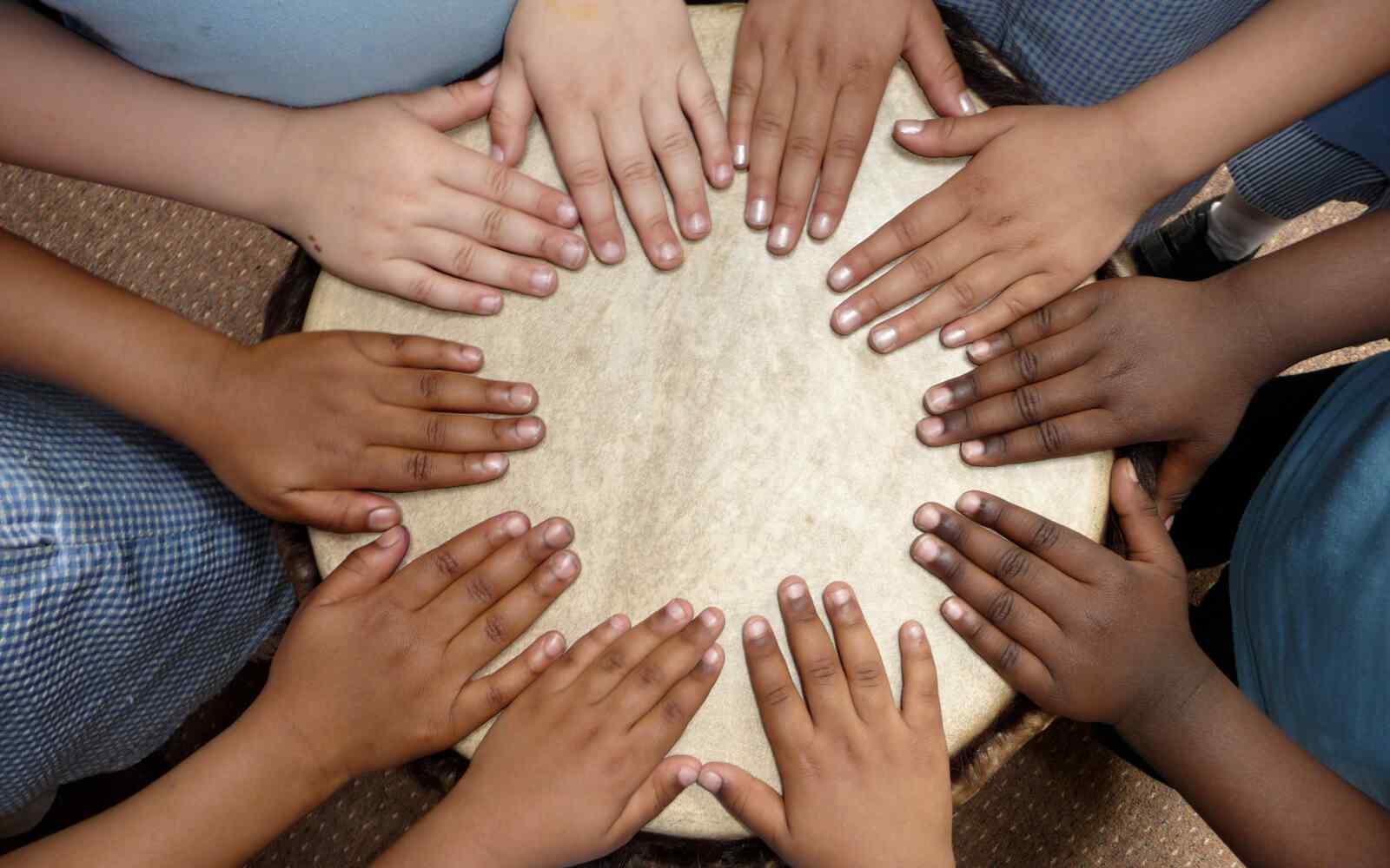 Hands of children on a djembe drum