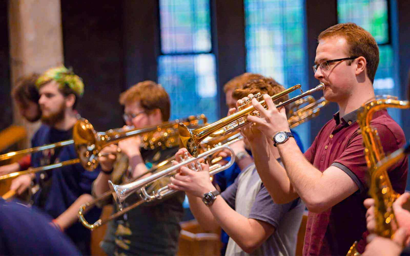 A group of students play brass instruments together in the university chapel.