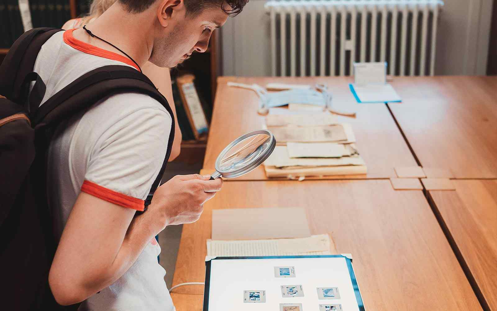 A student looking at artefacts through a magnifying glass