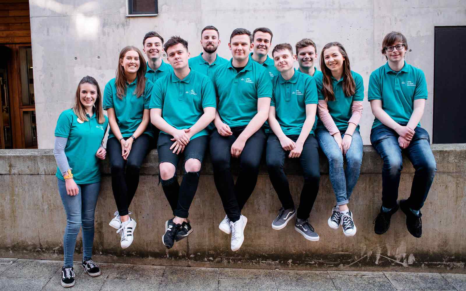 Group of student ambassadors sitting on wall and smiling.