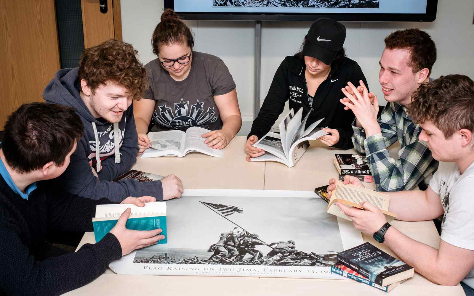 6 students sit around a table reading war studies books.