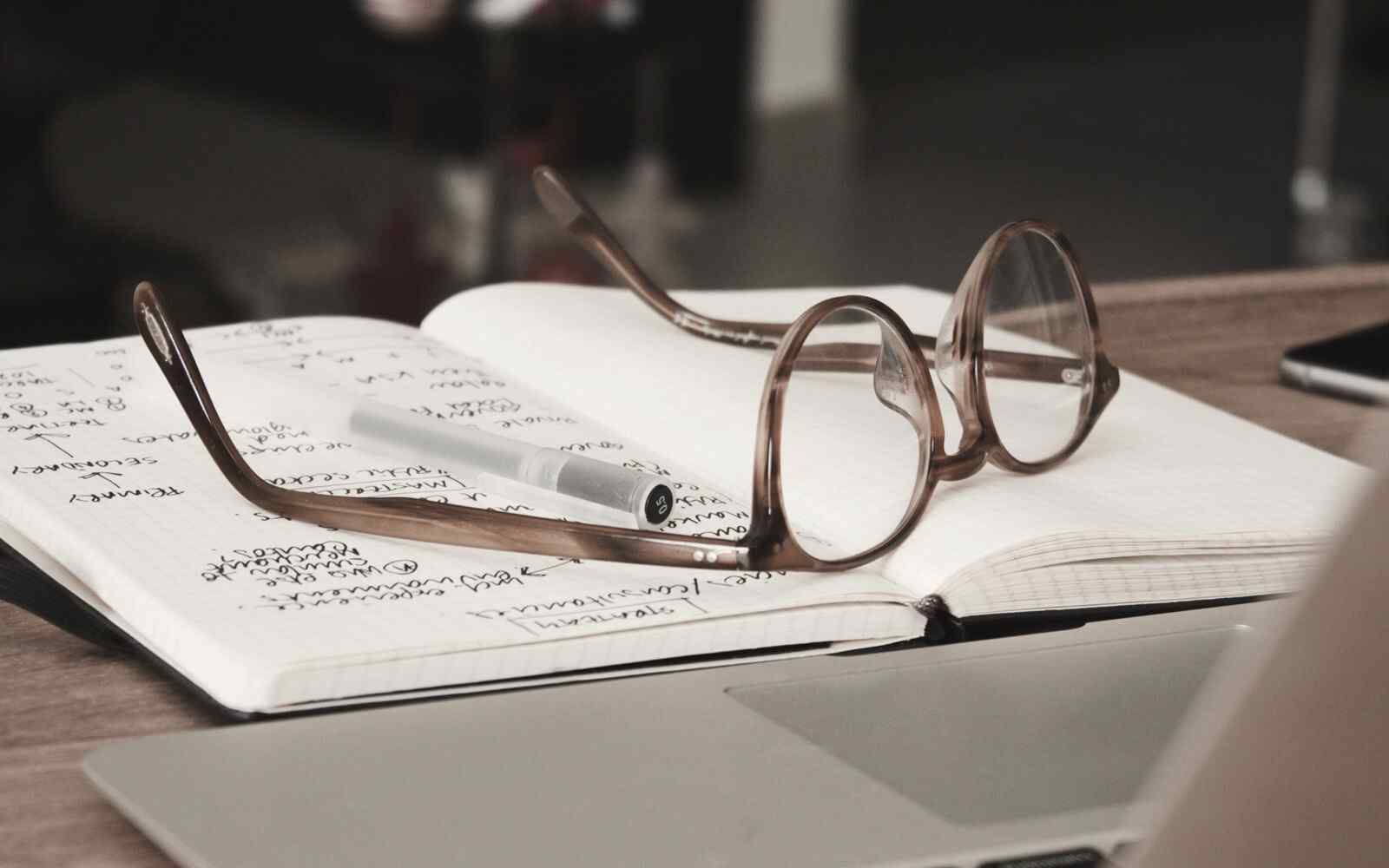 Open notebook with glasses on top