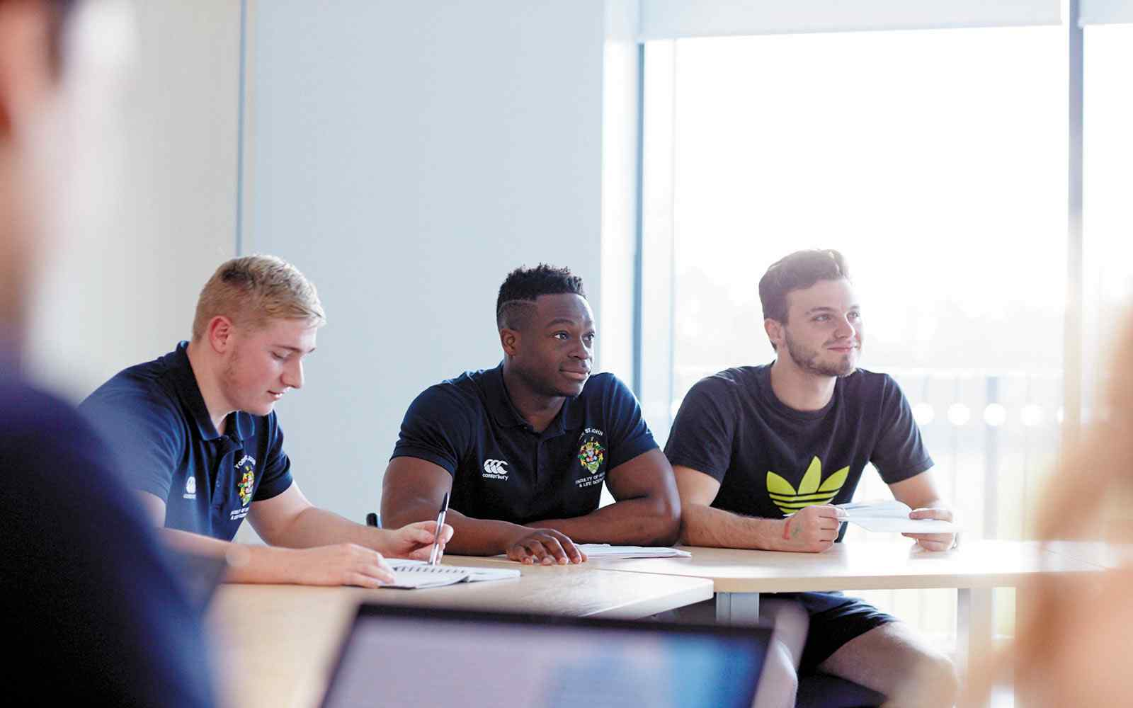 Three male students sitting at a desk paper is on the table. Two students are looking ahead, the other is looking downwards