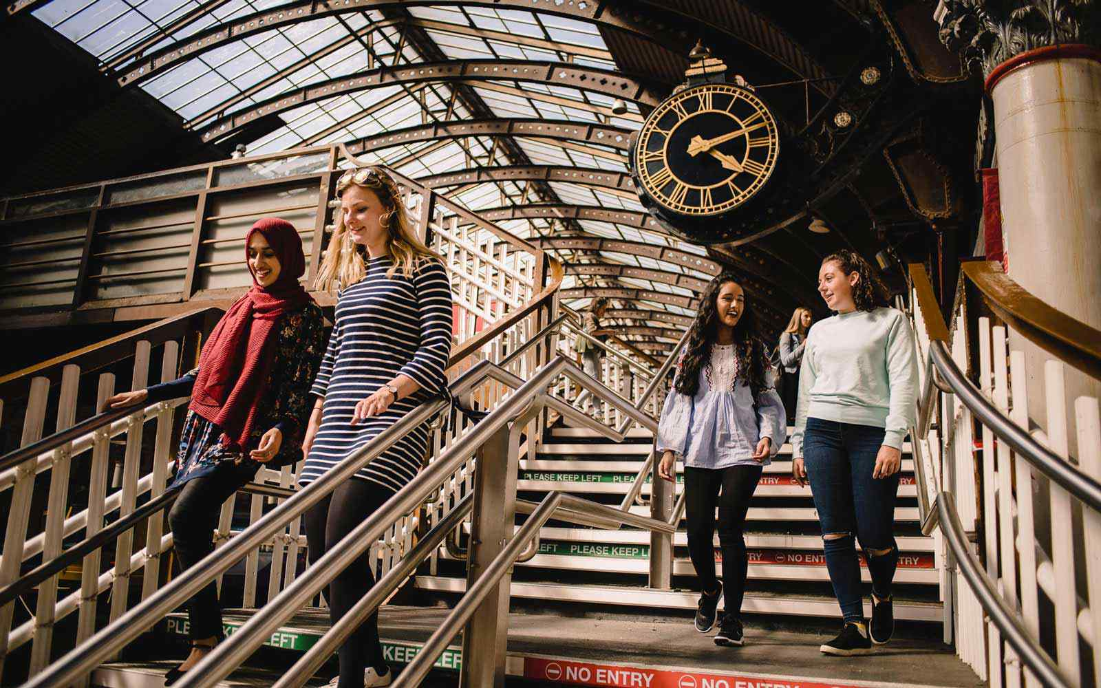Four students chat while walking down steps at York railway station.
