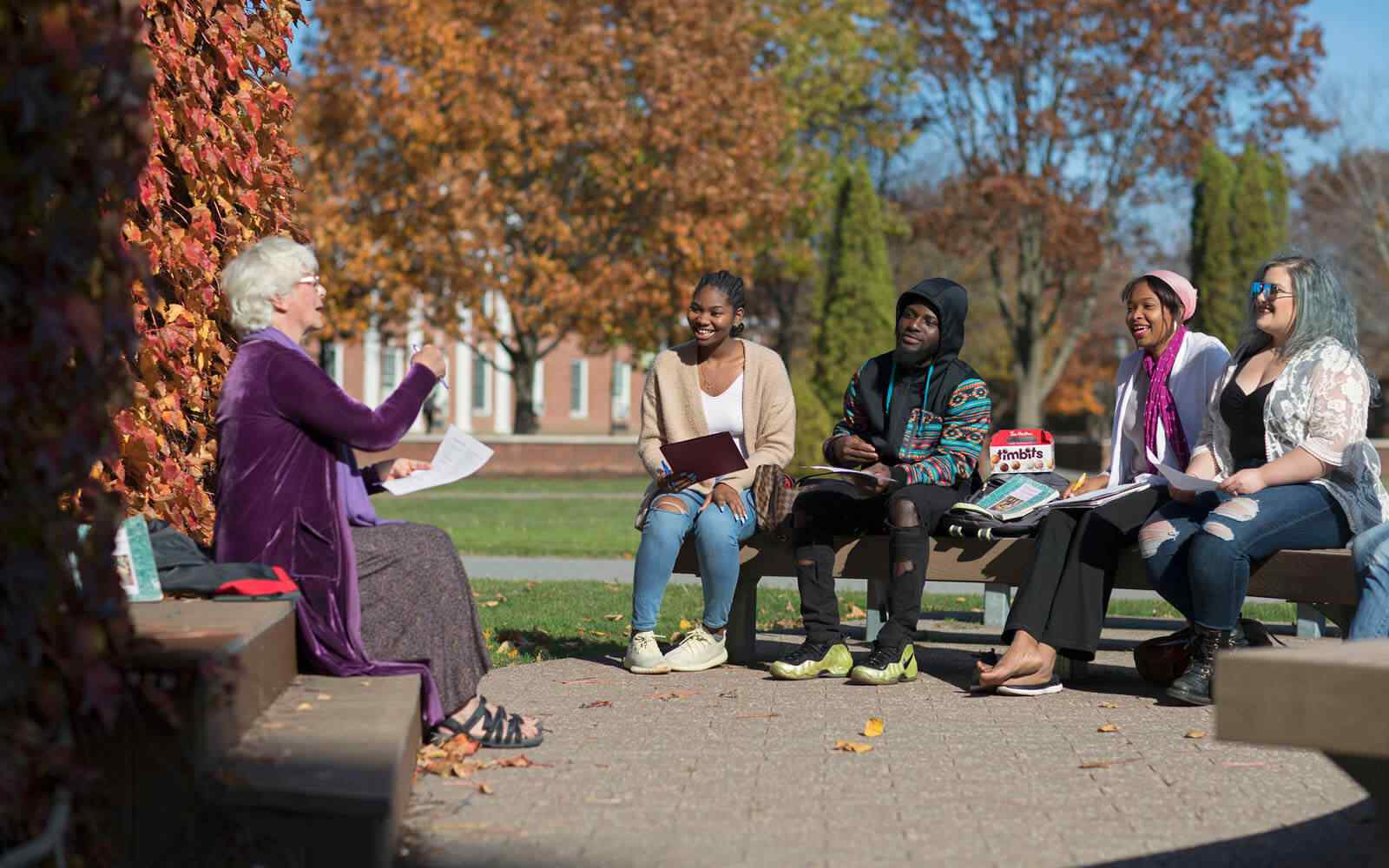Lecturer and students sat on benches in conversation at State University of New York