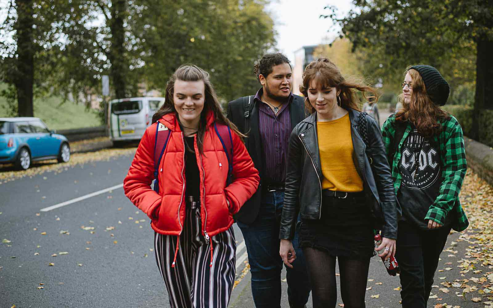 A group of four students walk and chat together outside the York St John campus.