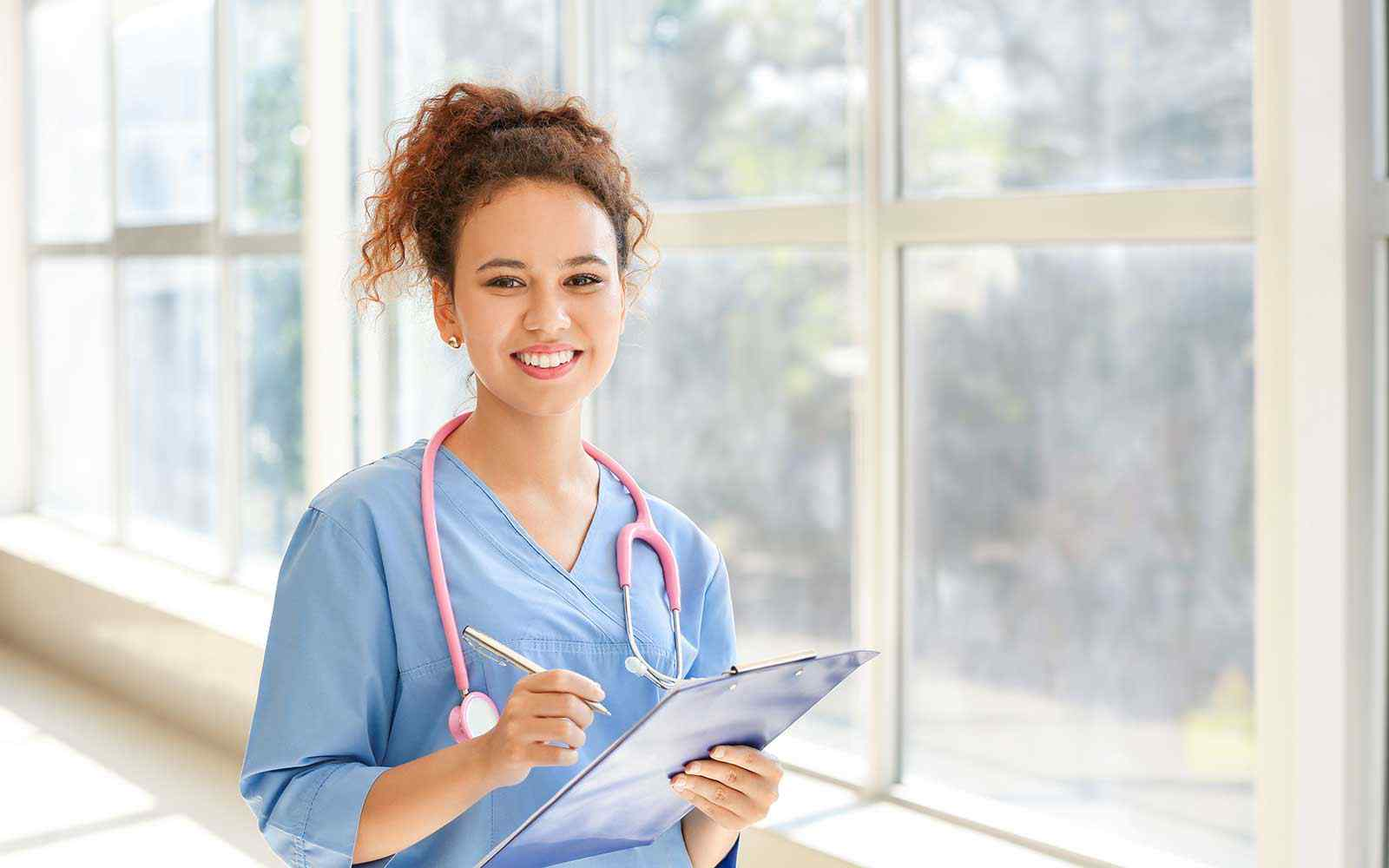 A student in scrubs smiles at the camera. She is holding a clipboard and stethoscope.