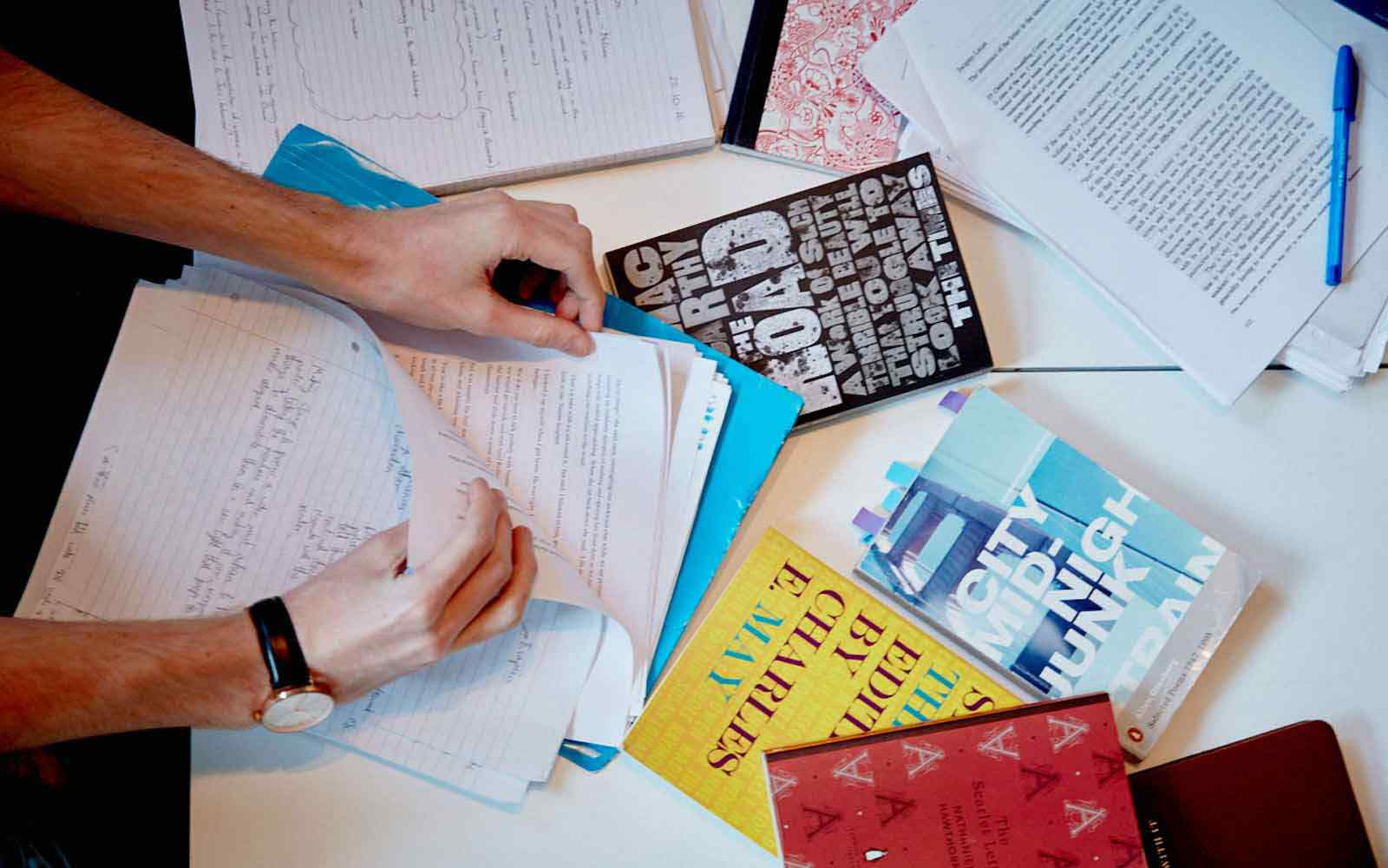 Table of study materials with hands picking up paper