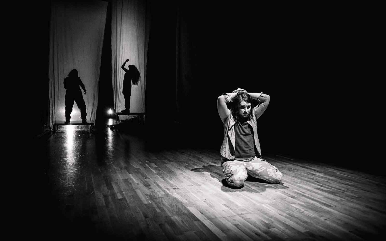 Black and white image of student acting, on floor with arms over head