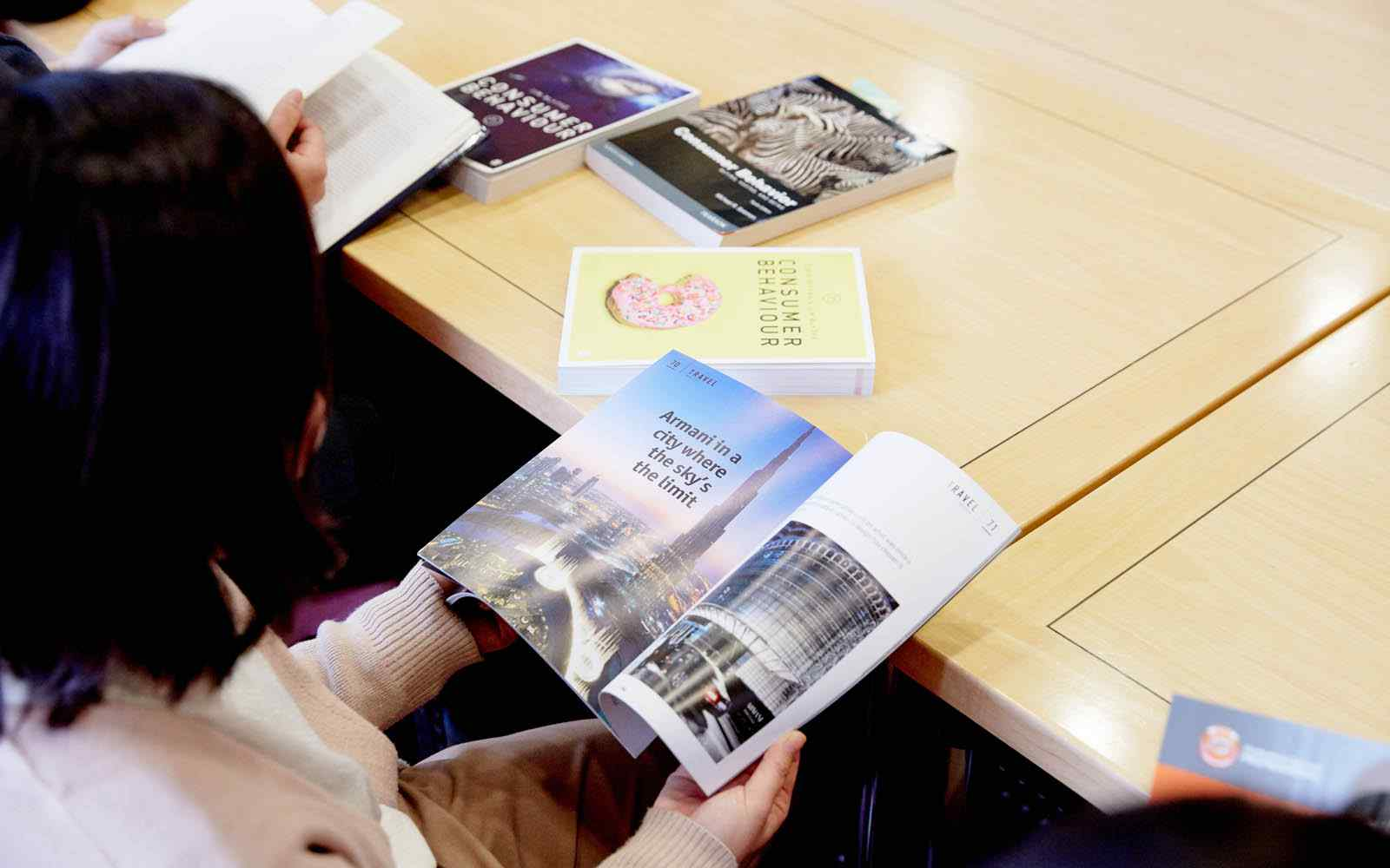 Student looking at travel advert in magazine