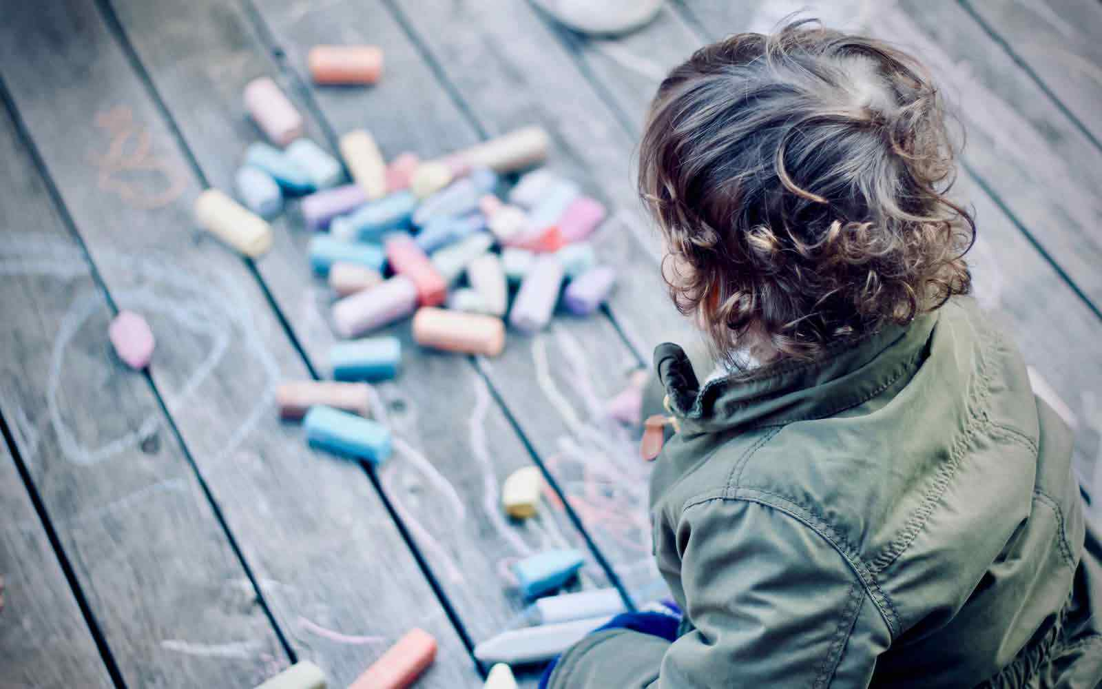 Child outside drawing with chalk