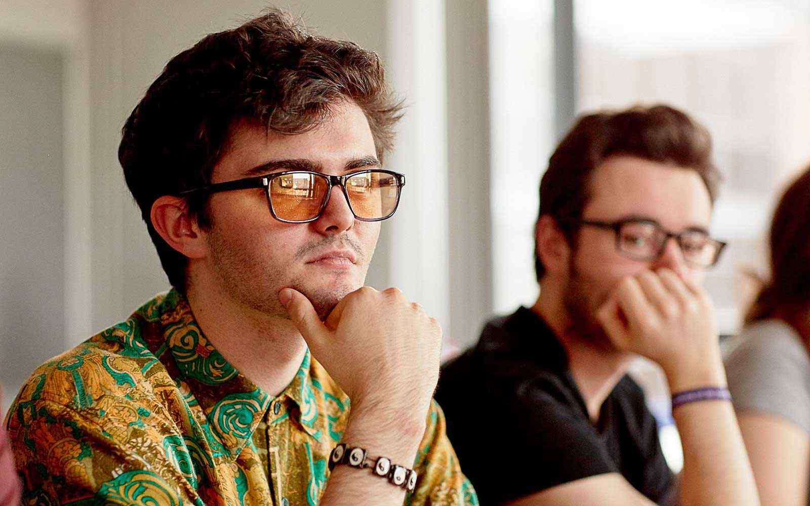 Two students in a lecture. both are wearing glasses