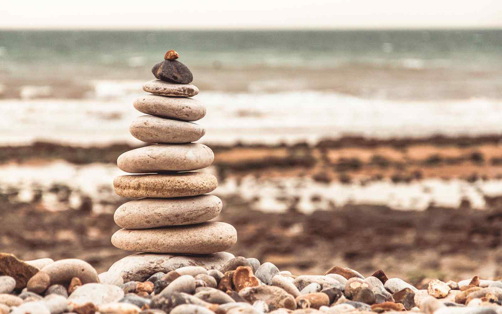 Tower of pebbles on a beach with the sea in the background