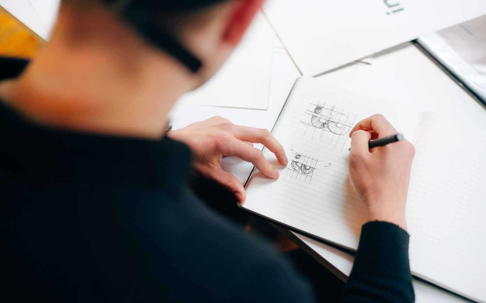 Student sketching in notebook