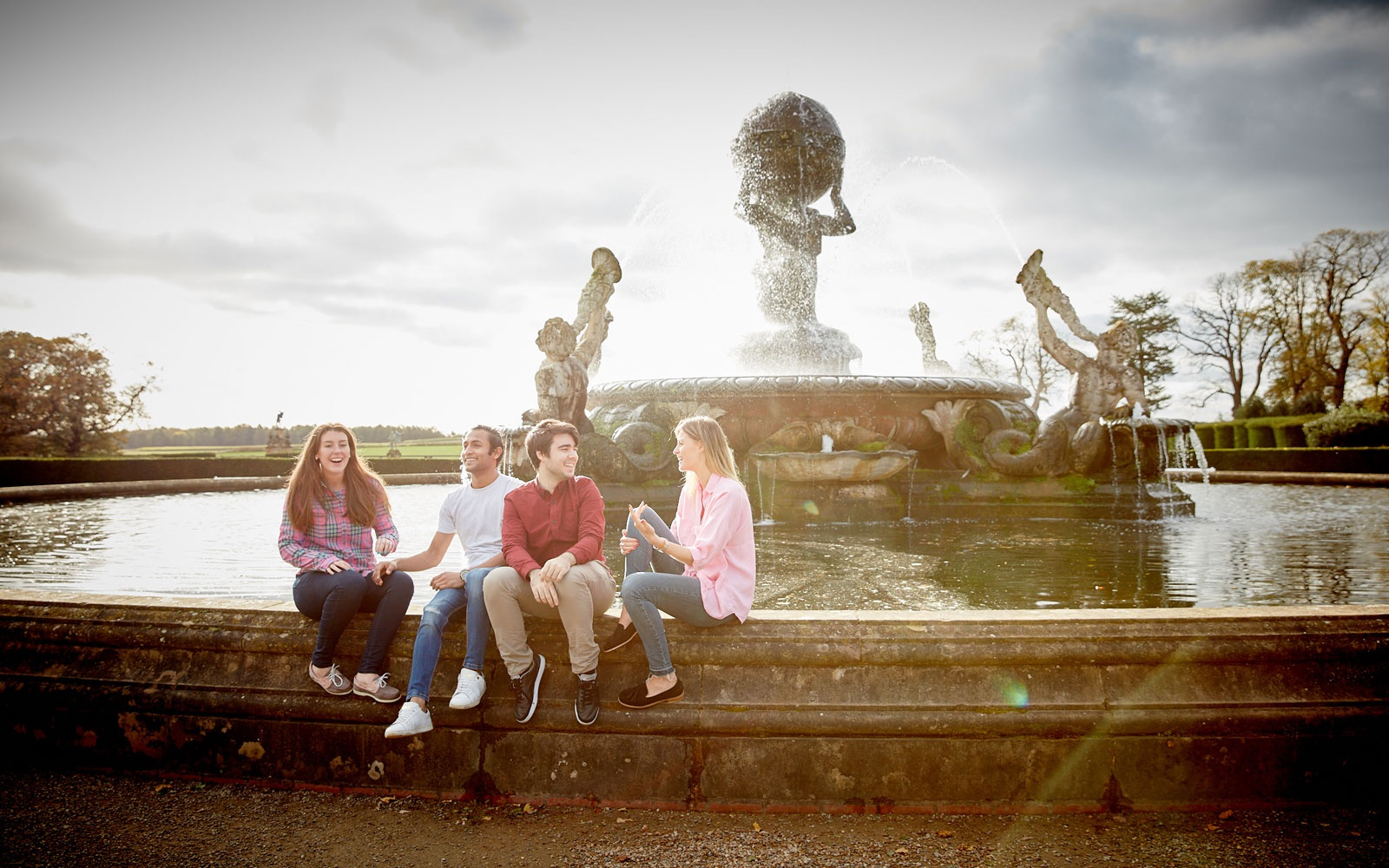 Students sitting on fountain at castle howard